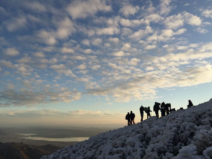 People standing on snow covered landscape against sky during sunset