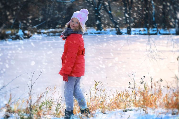 Full length portrait of girl standing on snow covered field during winter