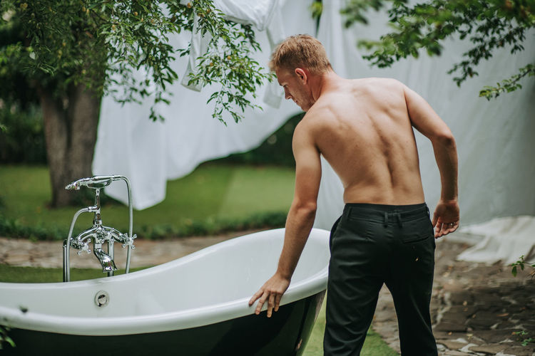 Midsection of man standing in bathroom