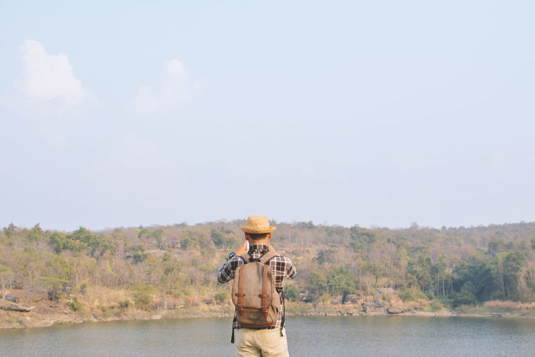 Rear view of man standing on riverbank against sky