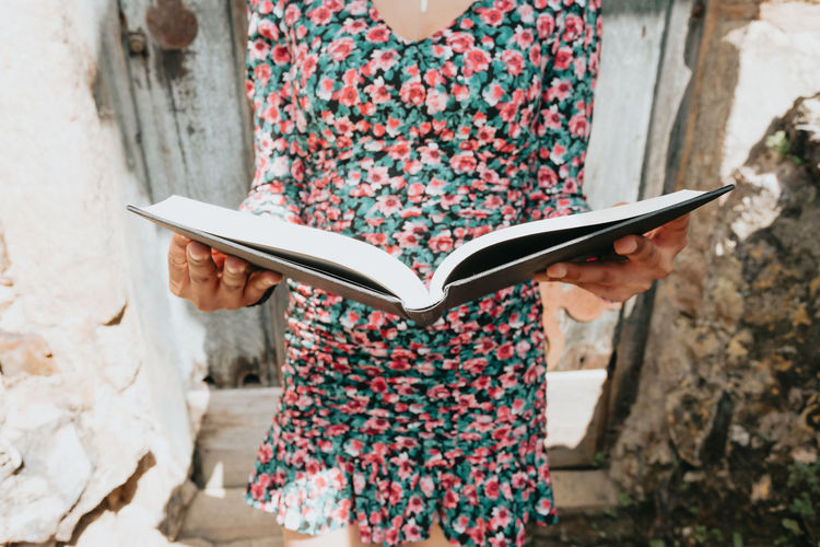 Midsection of woman holding book against wall