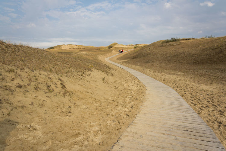 People walking through desert on a boardwalk