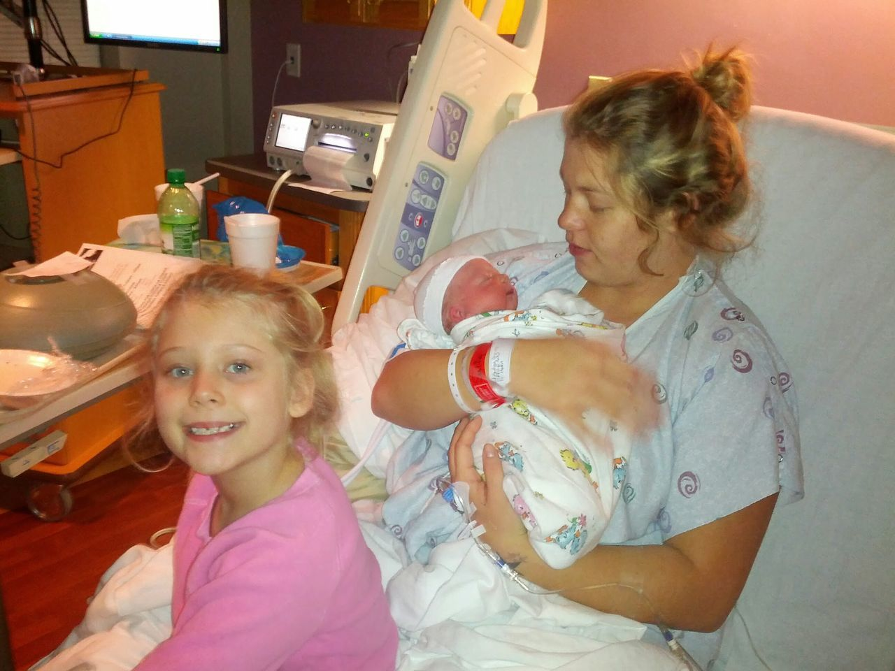 Portrait Of Girl Sitting By Mother Carrying Newborn Baby While Sitting On Bed In Hospital