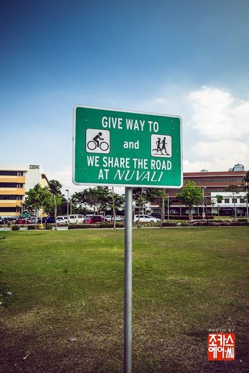 A sign promoting road sharing among bikers, runners and vehicles in a commercial developement complex. Signage Sign Road Sign Bike Runner Vehicle Commercial Centre  Santarosa Laguna Philippines Streetphotography Fujifilm Xe2 Fujixe2 Fujifilm_xseries Nuvali