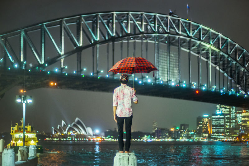 Woman standing on illuminated bridge at night