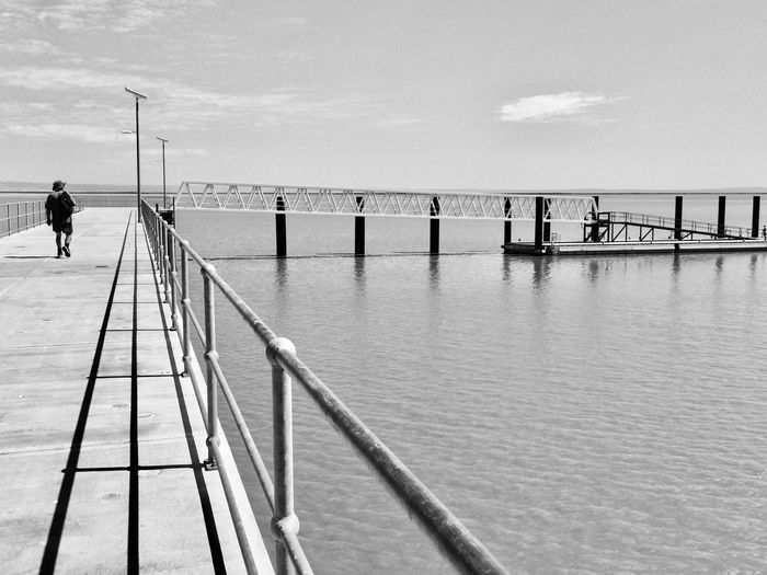 EyeEmNewHere Figure Walking By Water Man Walks Along Jetty Railing And Pier Shadows & Lights Black And White Photography Jetty Railing Lonesome Road Solitary Figure Solitude By The Water