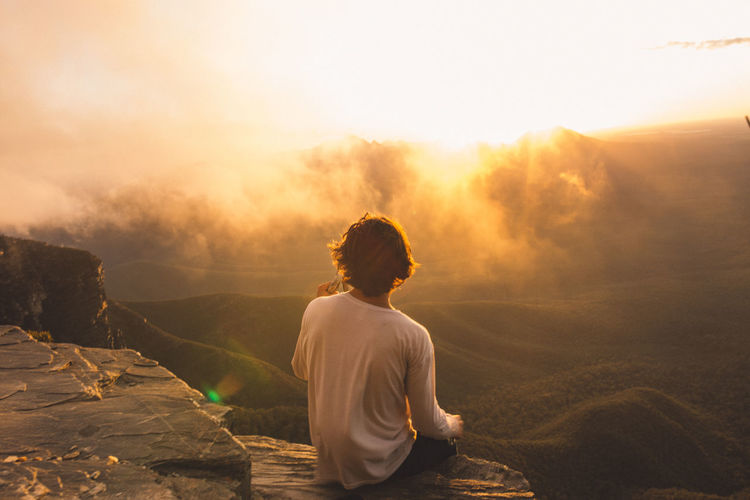 Rear view of man sitting on cliff while looking at landscape during sunset