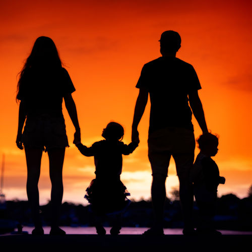 Silhouette friends standing against orange sky during sunset