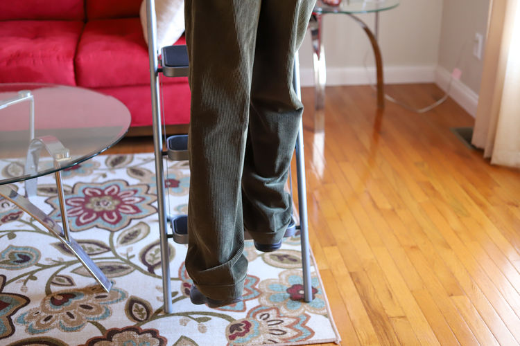Low section of man standing on floor at home