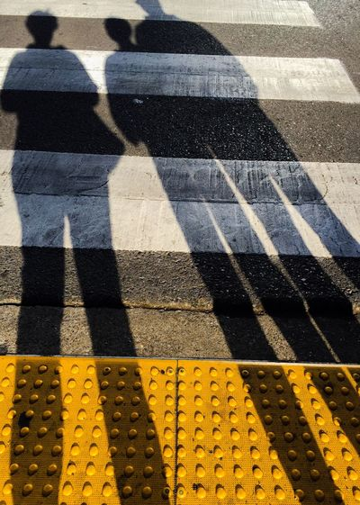 Shadow of people standing on road