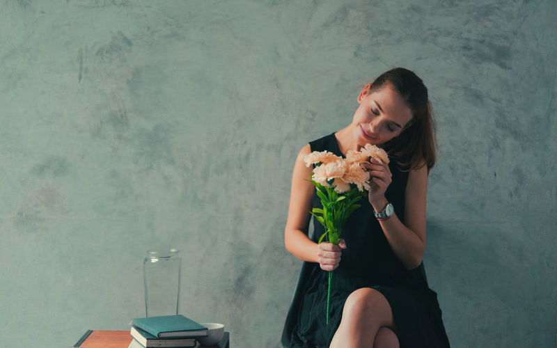 Woman holding flowers while sitting against wall