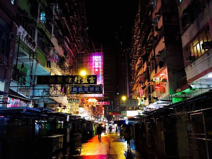 Illuminated city street amidst buildings at night