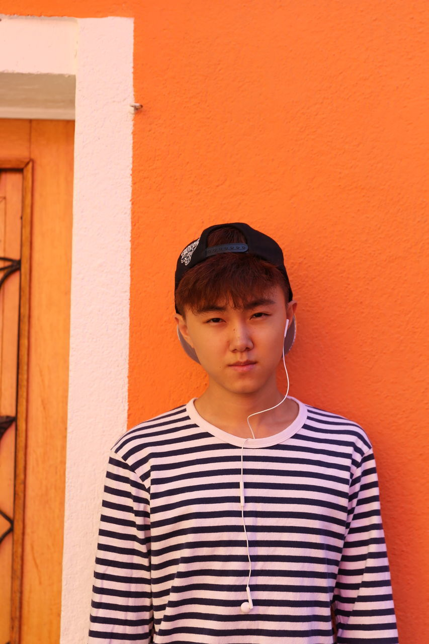 Portrait Of Boy Standing Against Orange Wall