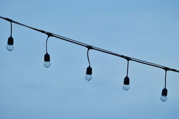 Low angle view of light bulbs hanging against clear sky
