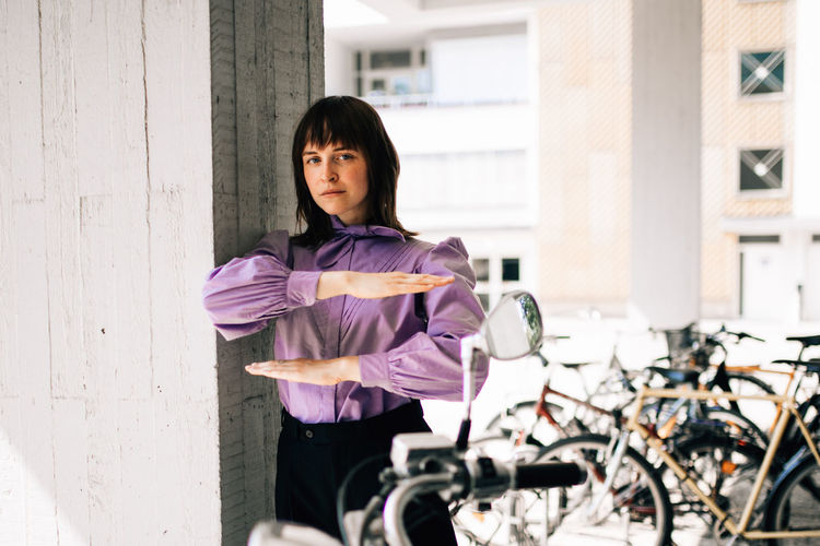 Portrait of young woman with bicycle standing against wall