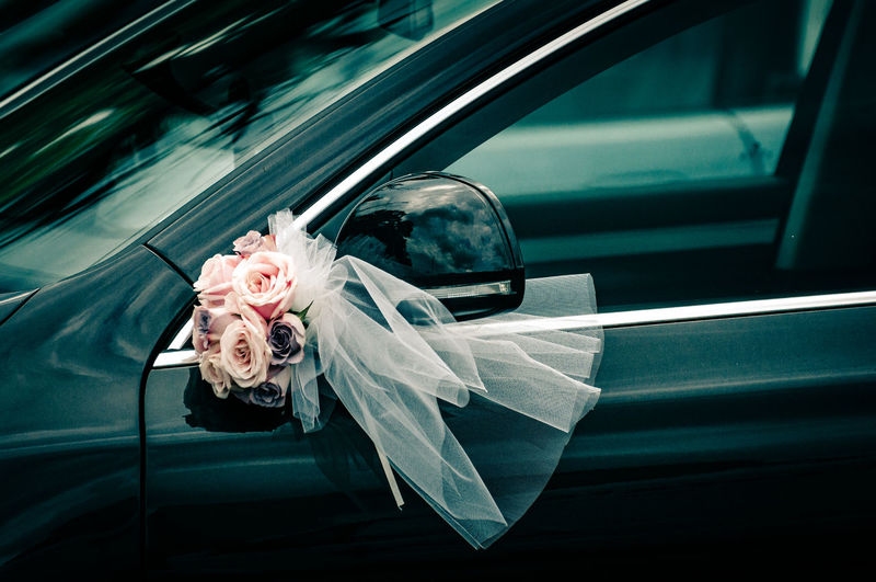 Rose bouquet with veil on side-view mirror of car