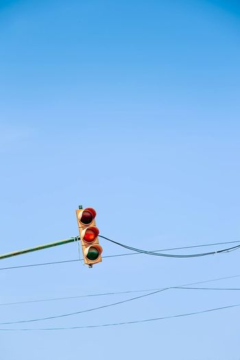 Low angle view of road signal on cables against clear blue sky
