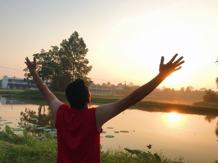Arms Outstretched Arms Raised Beauty In Nature Freedom Human Arm Lake Leisure Activity Lifestyles Limb Nature One Person Outdoors Plant Real People Rear View Sky Standing Sunset Tree Water
