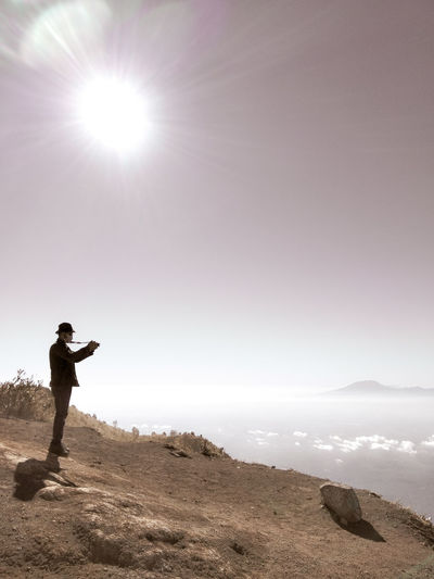 Man photographing while standing on mountain against sky