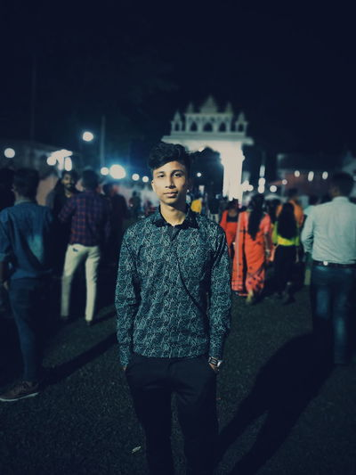 Portrait of young man standing city at night