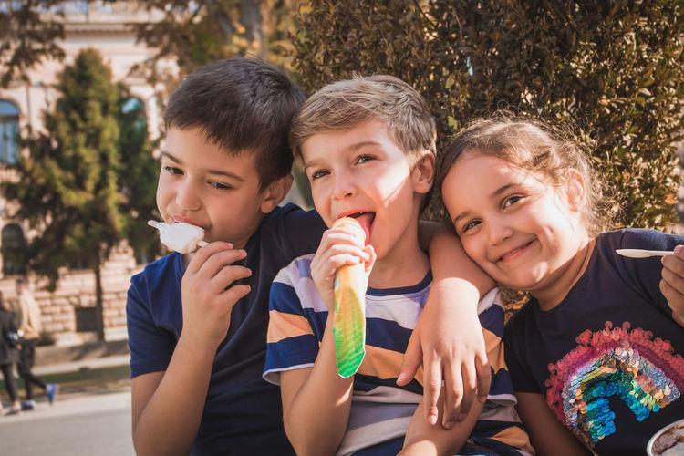 Portrait of cute siblings eating ice creams