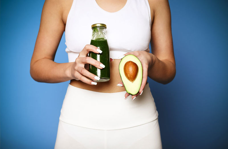 Midsection of woman holding drink against blue background