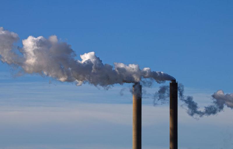 Chimneys Emitting Smoke Against Sky