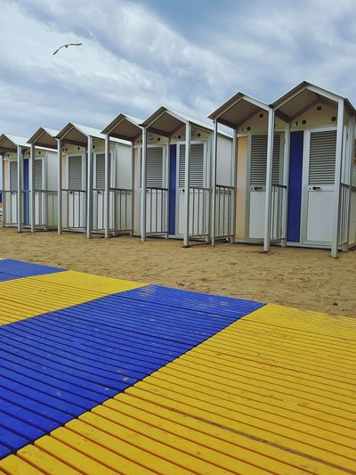 Beach Day Outdoors Sky Sea Multi Colored Sand Cloudy Day Beach Cabins Beach Huts In A Row Side By Side Seaside Blue And Yellow Stripes Colour Contrast Contrasting Colors Summer Summer At The Beach Paint The Town Yellow in Italy