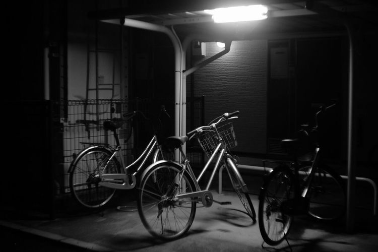 Bicycles parked at illuminated parking lot