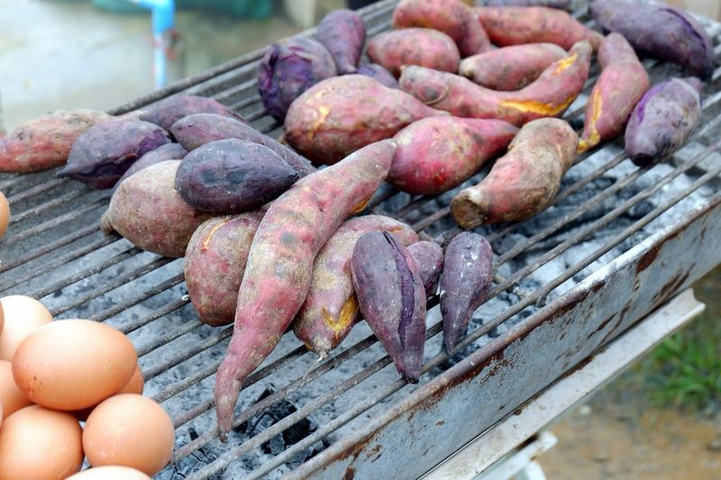 Close-up of sweet potatoes and eggs on barbecue grill