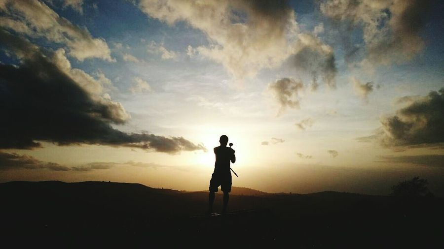 Silhouette man photographing against on field during sunset