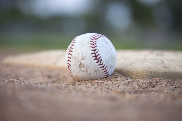 Close up view of a grungy baseball sitting near a base Ball Base Baseball Close-up Color Image Dirt Dirty Gravel Grunge Infield Low Angle View No People Old Photography Playing Field Selective Focus Sport View