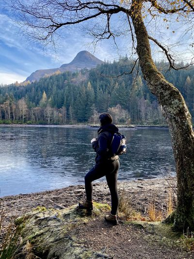 Full length of woman standing by lake against mountain and sky