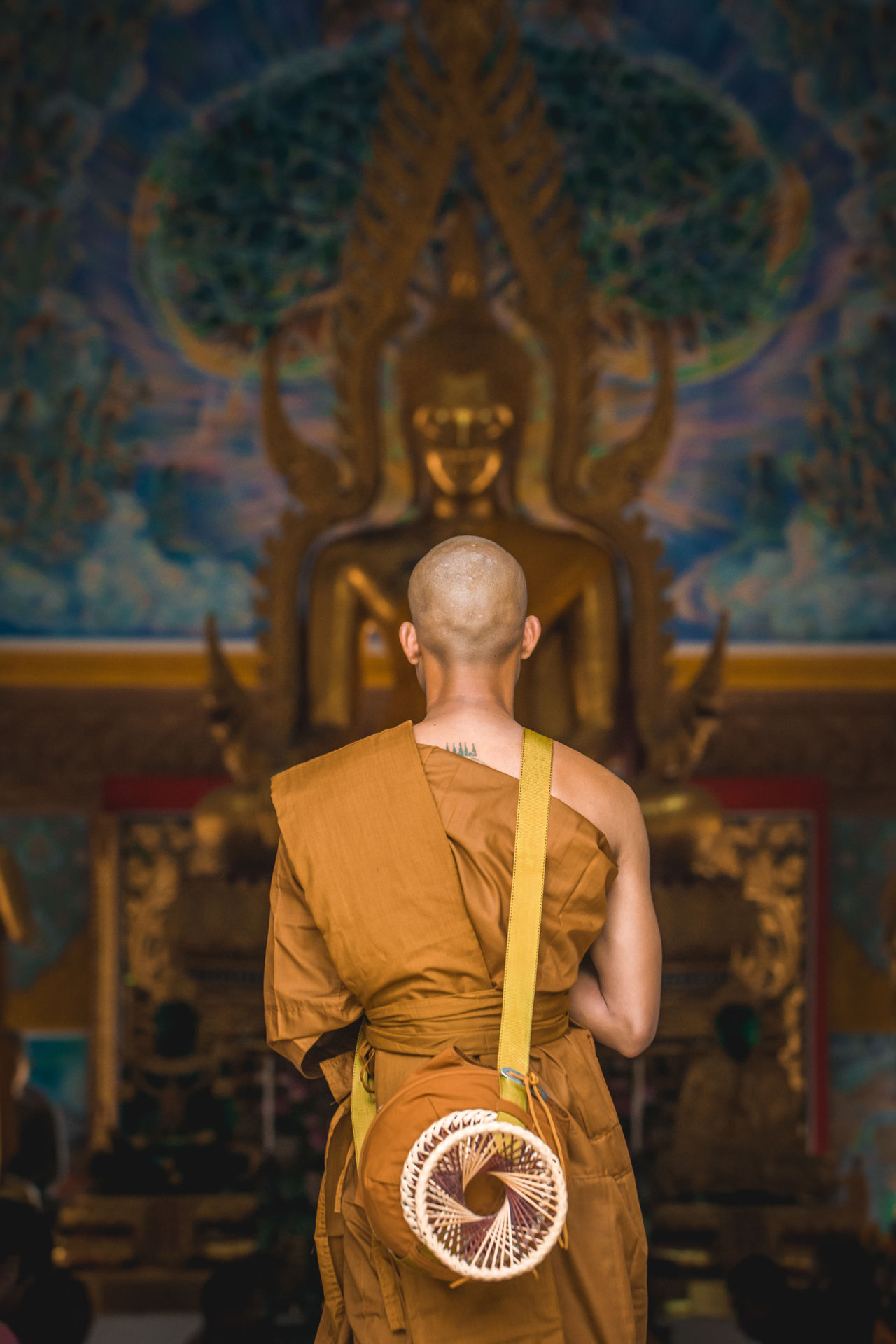 Rear view of monk standing against buddha statue in temple