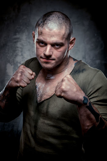 Portrait of man standing in fighting stance against gray background