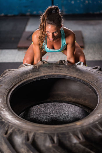 High angle view of mid adult woman carrying tire in gym
