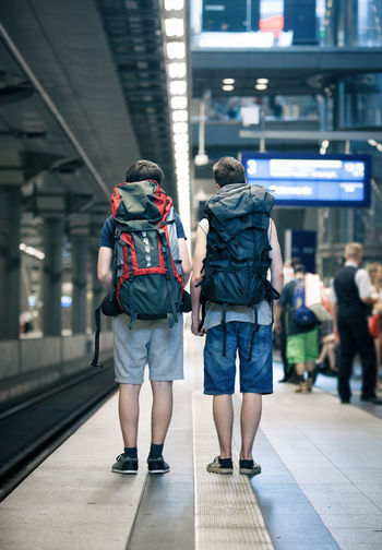 Going to see the World! Two Teenage Boys with backpacks, ready to get on a Train. Architecture Backpack Boys Built Structure Casual Clothing Full Length Future Holiday Indoors  Interrail Lifestyles Men People Real People Rear View Summer Teenagers  Train Station Transportation Travel Traveling Two People Vanishing Point