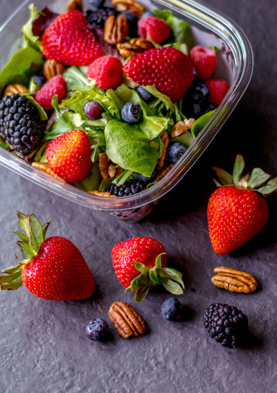 Fresh take out salad from the market. healthy eating on the go with greens, berries and pecans