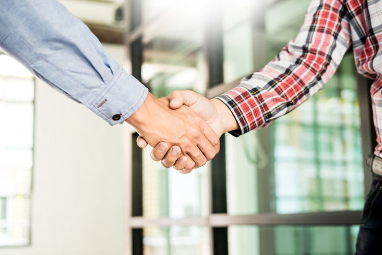 Midsection of man shaking hand with friend