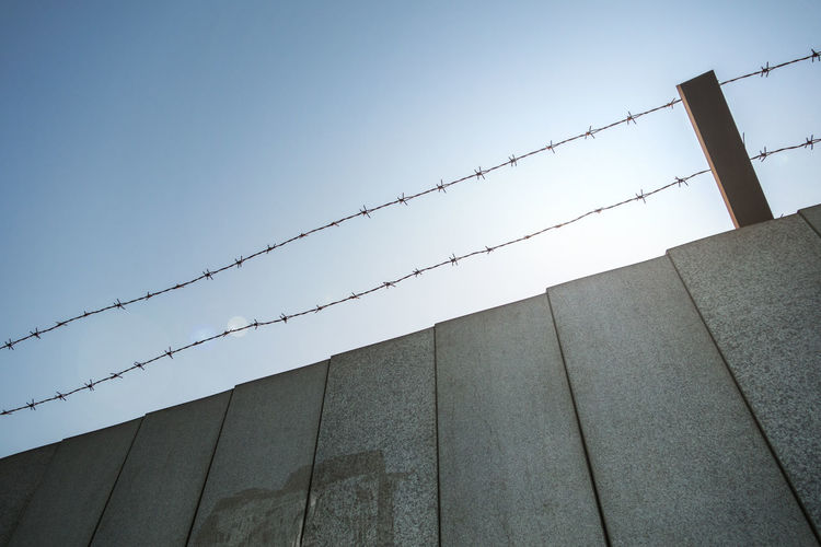 Low Angle View Of Barbed Wire Over Wall Against Clear Sky
