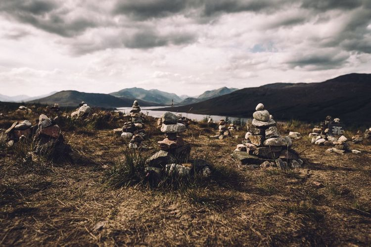Stacks Of Stones On Mountain Against Cloudy Sky