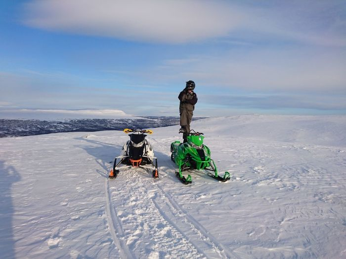 Full Length Of Man Standing By Snowmobiles On Snow Against Sky