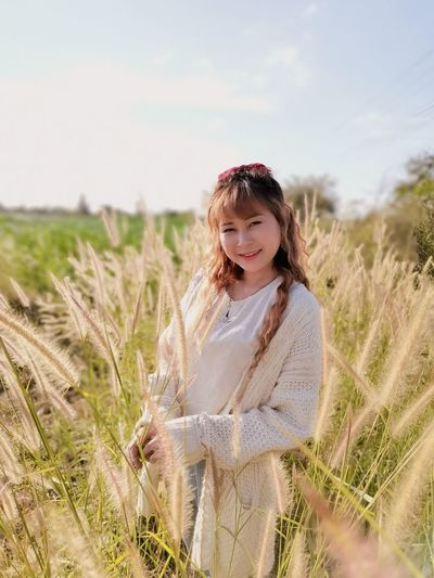 Portrait of a smiling young woman on field