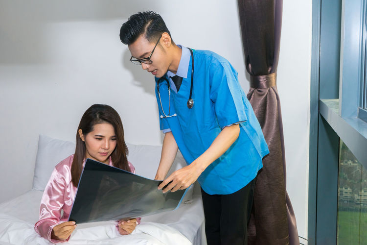 Doctor showing medical x-ray to patient sitting on bed at home