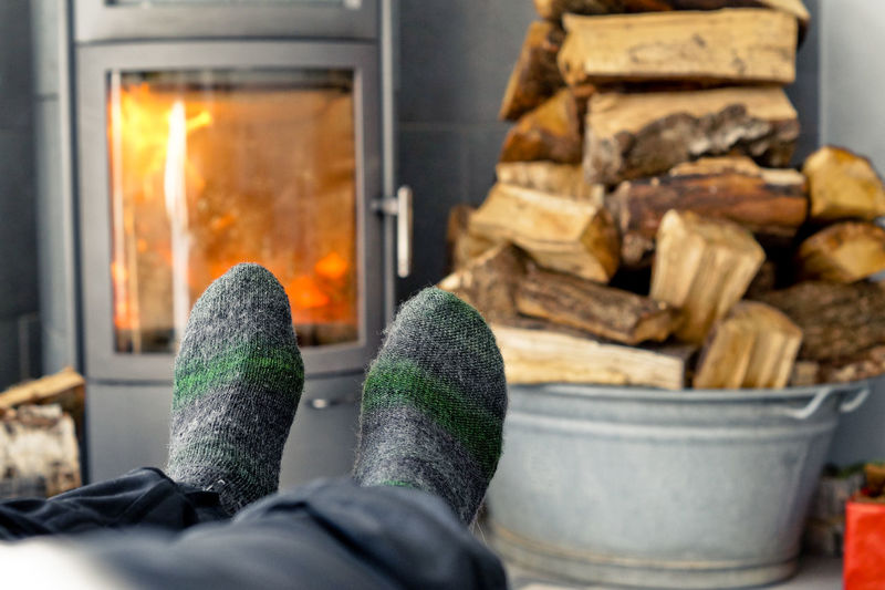 Low section of man wearing socks against firewood stack