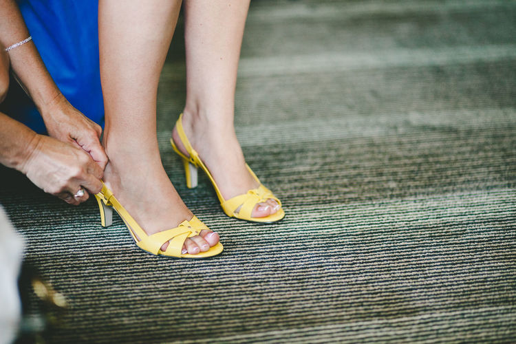 Cropped hands of woman assisting female friend wearing high heels on carpet
