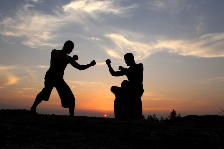 Silhouette men practicing boxing against orange sky during sunset