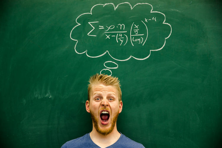 Man shouting with mathematical formula on blackboard