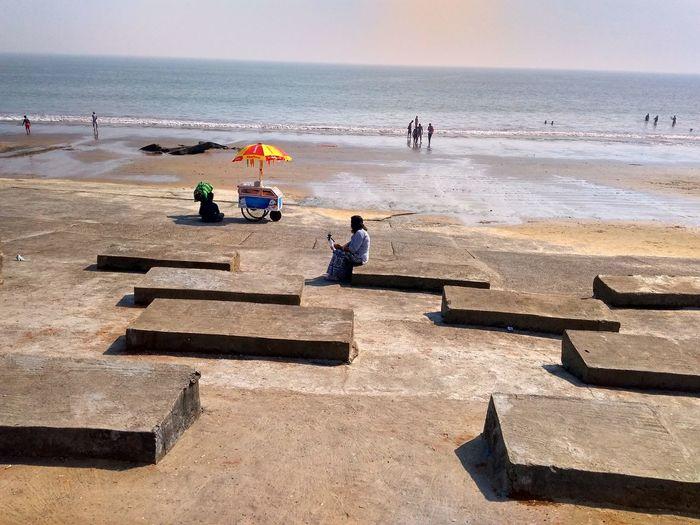 People enjoying of beach against sky