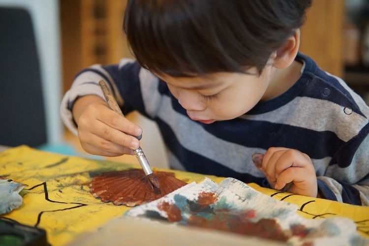 Close-up of boy painting at table